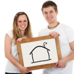 Young Couple Holding Sign with House